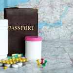 Tablets, passport on map background. Medical tourism concept.